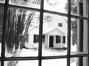 View of old Meetinghouse covered in snow as seen through window of brick Meetinghouse